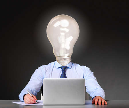 idea concept  businessman with bulb instead of his head is sitting at his table with laptop photo
