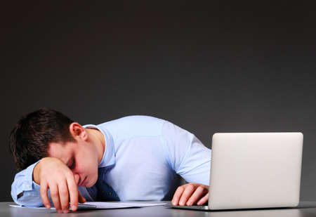 tired businessman is sleeping at his table with laptop photo
