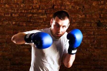 portrait of fighter in boxing pose against brick wall photo