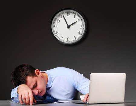 ノート パソコンで疲れたビジネスマンは彼のテーブルで眠っています。 写真素材