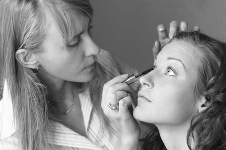 make up stylist is applying cosmetics photo