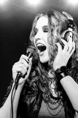 woman is singing rock song with a microphone photo