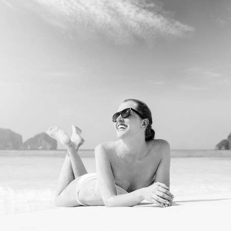 young woman is lying on beach photo