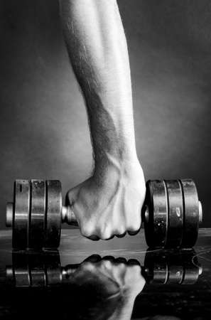 male hand is holding metal barbell on dark gray background Stock Photo