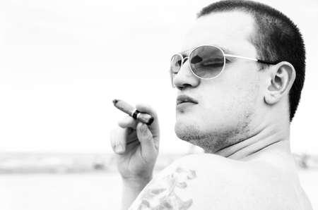looking sideways: handsome man with cigar on beach is looking sideways Stock Photo