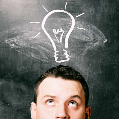 creative ideas: idea  man is looking up with chalk board behind him Stock Photo