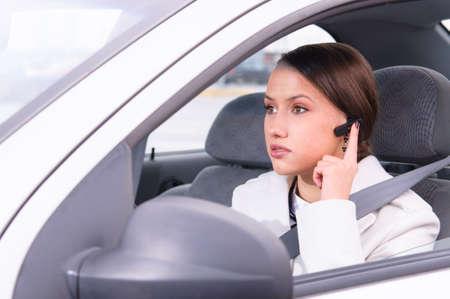 mooie vrouw driver is veilig praten telefoon in de auto met behulp van een headset