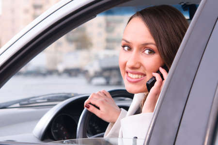 sensual young woman is looking at camera from a car and talking phone photo