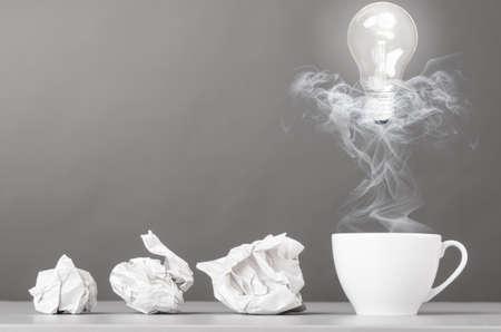 creatief proces verfrommelde proppen en kop op grijs Stockfoto