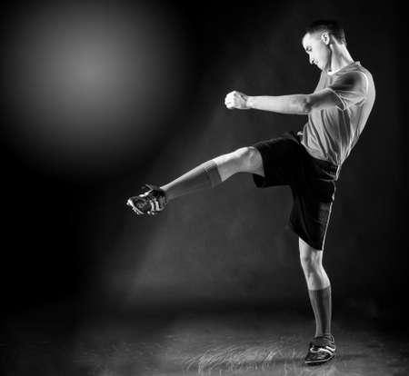 football socks: handsome soccer player kicks ball on black background Stock Photo