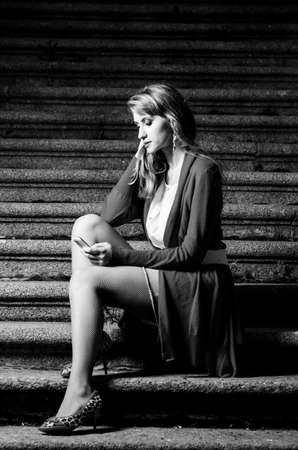 fashionable woman with mobile phone in hands is sitting on stairs at evening photo