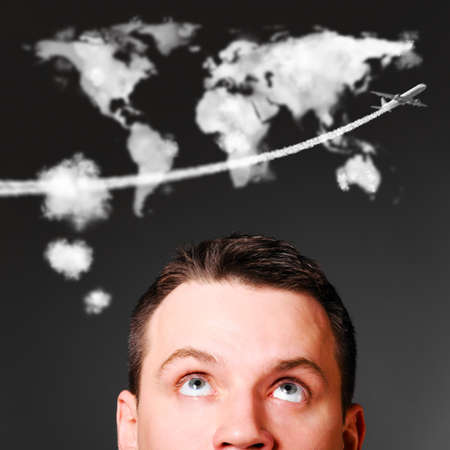 man is looking up at world map shaped clouds photo