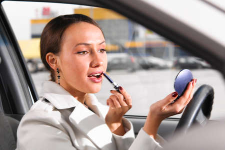 elegant woman is doing makeup on the run in her car photo