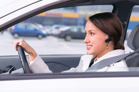 beautiful woman driver is safely talking phone in a car using a headset photo