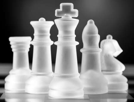 field glass: glass chess pieces is standing on board in dark