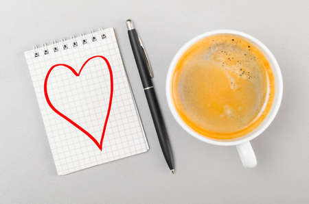 heart failure: love  notebook with heart picture and cup on gray