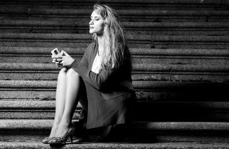 fashionable woman is sitting on stairs at evening photo