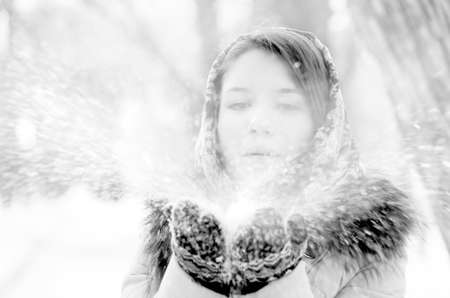young woman is blowing snow in winter park photo