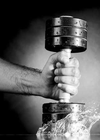 mannelijke hand houdt metalen barbell op donkere grijze achtergrond