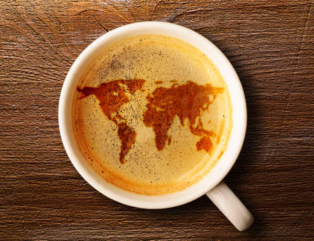world map on cup of fresh espresso on table, view from above photo