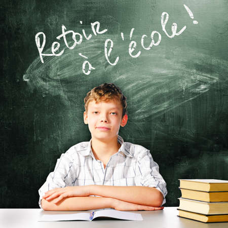 him: school boy is sitting at table with chalk board and back to school in french caption behind him