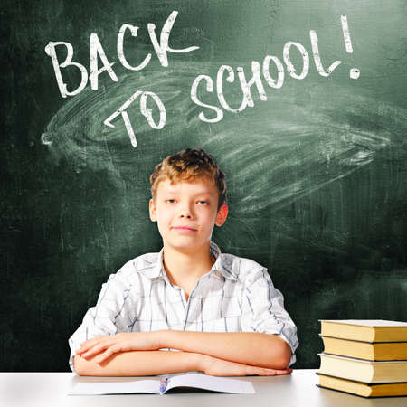 school boy is sitting at table with chalk board and back to school caption behind him photo
