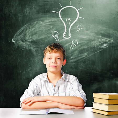 thin bulb: school boy is sitting at table with chalk board behind him