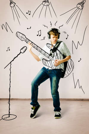 smart boy: teenager is playing on drawn guitar at concert