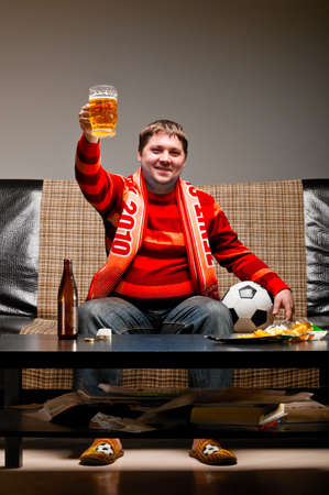 soccer supporter is sitting on sofa in red jersey photo