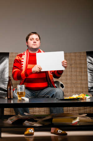 watching football: soccer supporter is sitting on sofa in red jersey Stock Photo