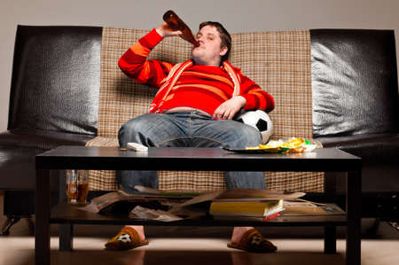 soccer supporter is sitting on sofa in red jersey Stockfoto