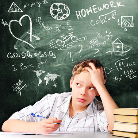 school boy is sitting at table and thinking with chalk board behind him Stock Photo - 21912602