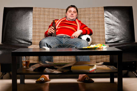 soccer supporter is sitting on sofa in red jersey Standard-Bild