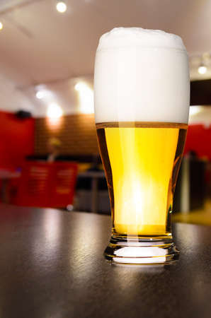 draught: glass of fresh draft lager beer on table in pub