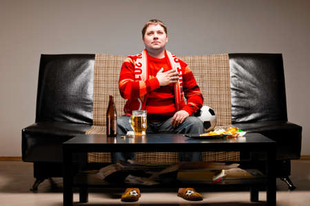 man in chair: soccer supporter is sitting on sofa in red jersey Stock Photo