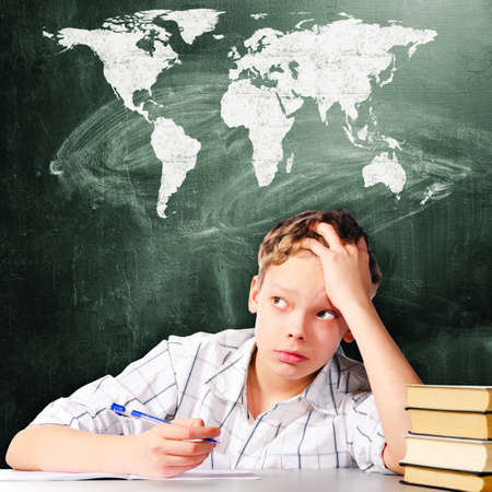 school boy is sitting at table and thinking with chalk board behind him Stock Photo - 21913342