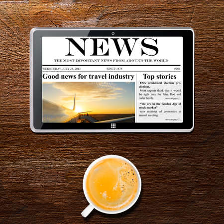 tablet computer with news and cup of coffee on table, view from above photo