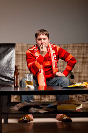 soccer supporter is sitting on sofa in red jersey Stock Photo