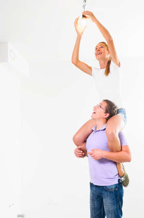 happy couple are fixing bulb at their new empty apartment photo