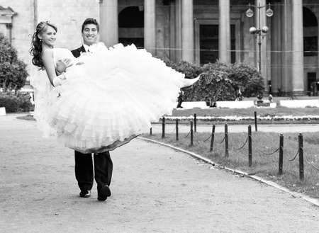 groom is carrying bride on arms on city park road photo