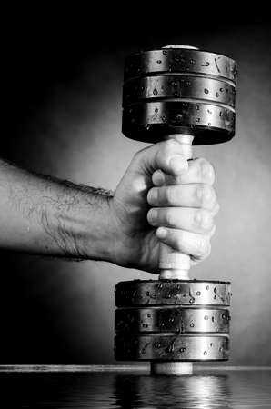 male hand is holding metal barbell on dark gray background photo