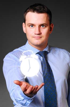 caucasian businessman is holding alarm clock in hands photo