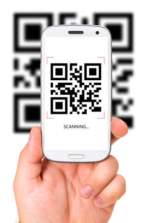 male hand is holding a modern touch screen phone and scanning QR code  photo