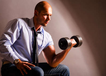 strong business man is raising a dumbbell photo
