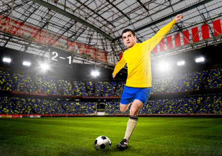 soccer boots: soccer or football player is kicking ball on stadium Stock Photo