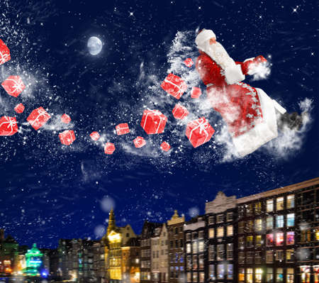 santa claus is flying with snow and gift boxes on deep red background photo