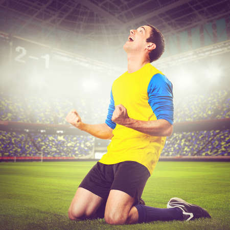 soccer or football player is celebrating goal on stadium, warm colors toned photo