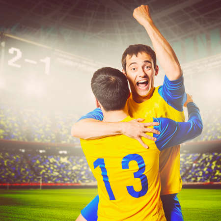 colores calidos: jugadores de f�tbol o de f�tbol celebran el gol en el estadio, los colores c�lidos en tonos Foto de archivo