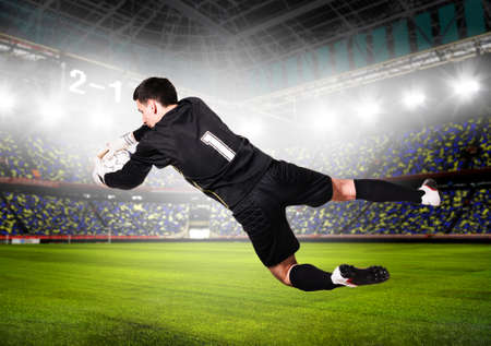 soccer or football goalkeeper is catching ball on stadium