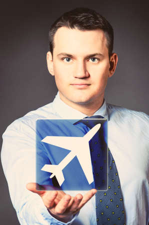 caucasian businessman is holding airplane icon in hands photo